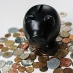 black colored piggy bank on top of a pile of coins