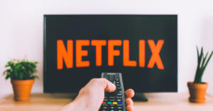 viewer holding a remote control pointed towards a television screen displaying the Netflix logo